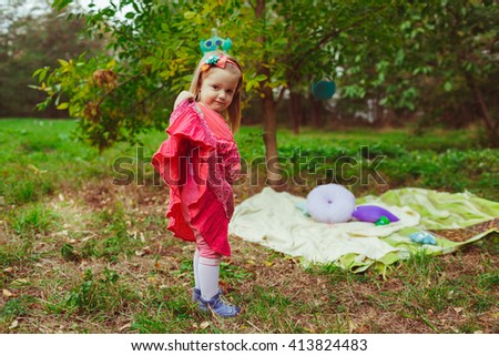 Girl in the pink dress  stands next to the tree - stock photo