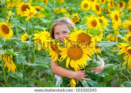 Girl in the sunflowers field with sunflowers - stock photo