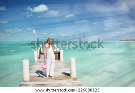 Girl in the white dress on the wooden jetty, Great Exuma, Bahamas  - stock photo
