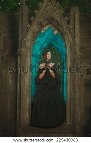 Girl in the window of the castle stands the night in the Gothic manner. - stock photo