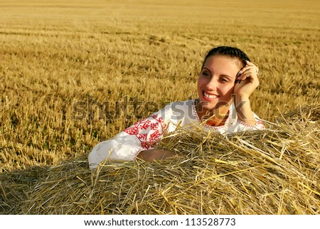 girl in traditional Russian costume lying on a haystack and smiling, space for text - stock photo
