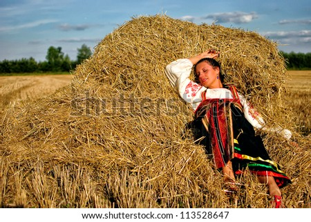 girl in traditional Russian costume resting on a haystack - stock photo
