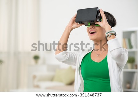Girl in VR device enjoying her time in videogame - stock photo