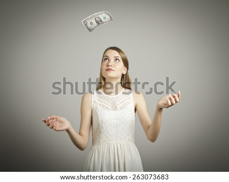Girl in white and falling dollar banknote. Currency and lottery concept. - stock photo