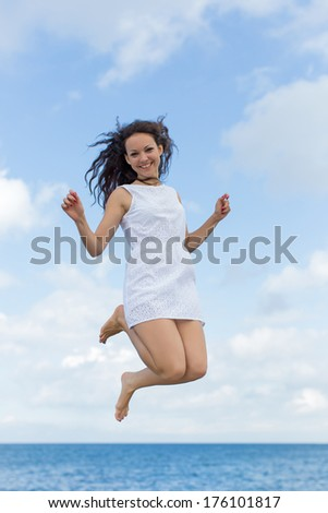 Girl in white at the sea. Young woman jumping outdoors looking at camera smiling - stock photo