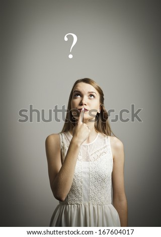 Girl in white full of doubts and hesitation. Girl and question mark above her head. - stock photo