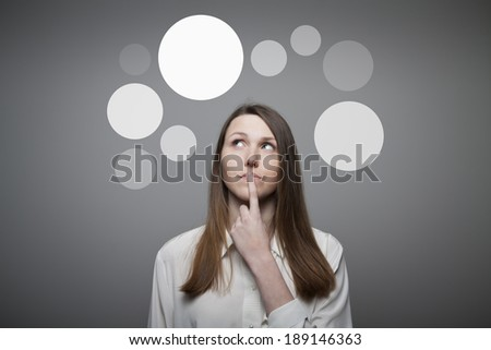Girl in white having an idea with gray bubbles over her head. - stock photo