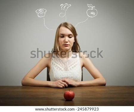 Girl in white sitting in front of an apple. Doubt or fast food concept. - stock photo