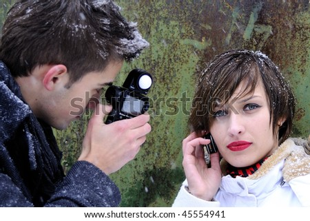 girl in winter and young photographer - stock photo