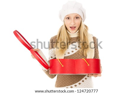 Girl in winter cap holding a gift and is surprised - stock photo