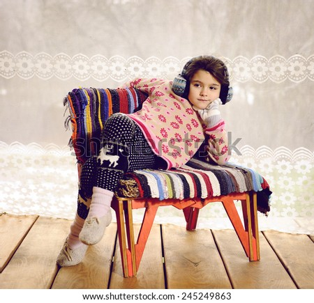 Girl in winter clothes on the porch of a country house - stock photo