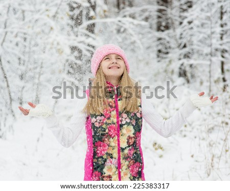 girl in winter forest enjoying snowfall - stock photo