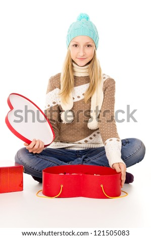 girl in winter hat sitting with gift boxes - stock photo