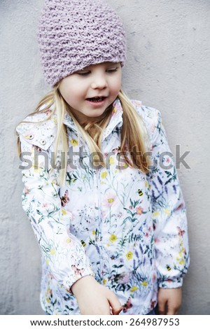 Girl in woolly hat and flowery jacket looking down - stock photo