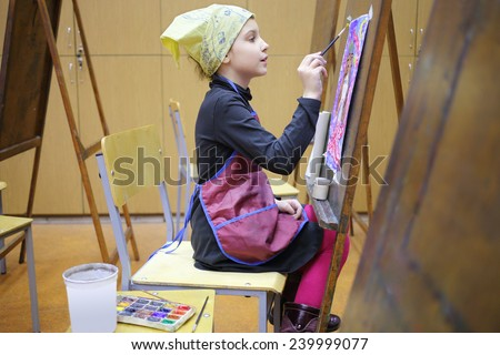 Girl in yellow scarf and apron painting colorful picture in art class - stock photo