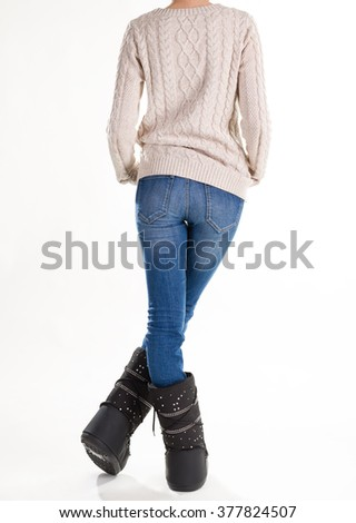 Girl is back in winter clothes. Girl dressed in moon boots, knitted sweater and jeans. - stock photo