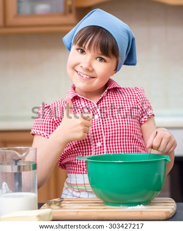 Girl is cooking in kitchen and showing thumb up sign, indoor shoot - stock photo