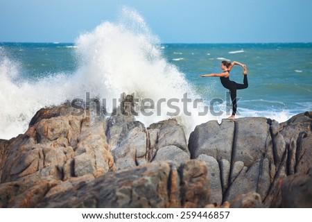 girl is doing yoga, standing in Lord of the Dance pose (Natarajasana) on rocks near crashing wave - stock photo