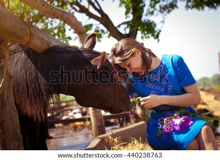 Girl is feeding a horse on the farm - stock photo