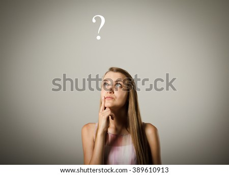 Girl is full of doubts and hesitation. Girl and question mark above her head. - stock photo