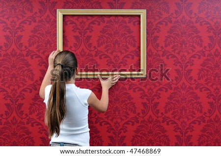 girl is hanging up a picture frame - stock photo
