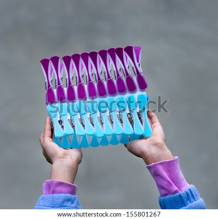 Girl is holding clothespins - stock photo