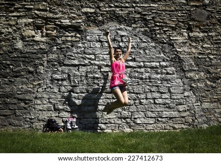 girl is jumping near the brick wall - stock photo