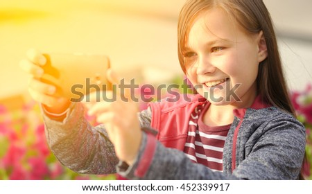Girl is making photo using a phone, outdoor shoot - stock photo