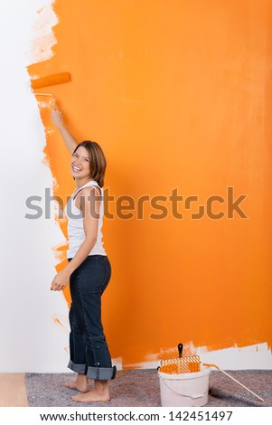 Girl is painting her apartment with orange color - stock photo