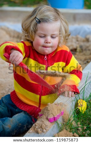 girl is playing in a sandbox - stock photo