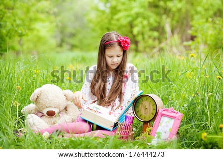 girl is reading fairytale book outdoors - stock photo