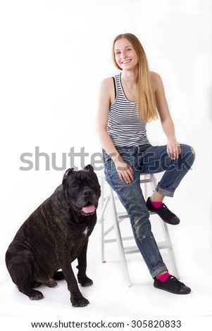 girl is sitting on a stepladder. her dog Cane Corso next. isolate - stock photo
