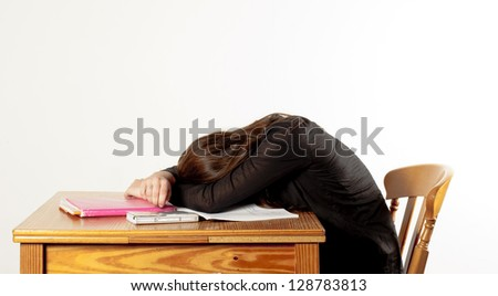girl is sleeping while studying, with her head on the table - stock photo