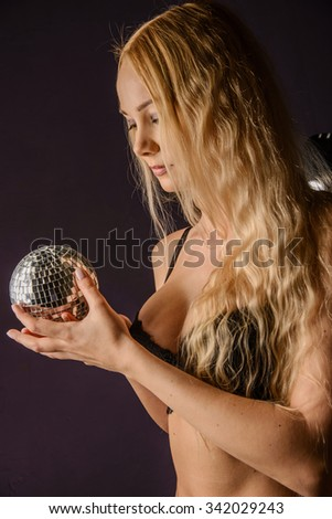 girl is standing back holding mirror ball over black background - stock photo