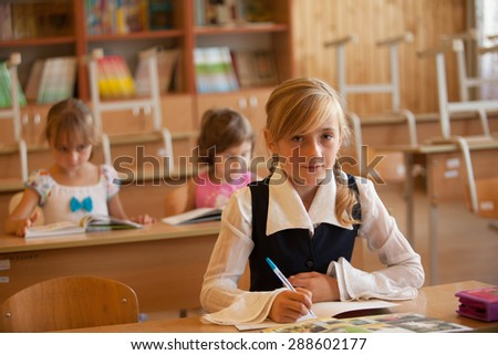 Girl is studying in classrom at the desk - stock photo