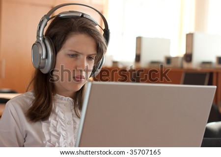 Girl is using computer with headphones - stock photo