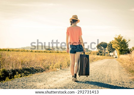 Girl is walking with her suitcase during her holiday - people, holidays and lifestyle concept - stock photo