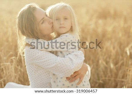girl is with her mother in the autumn field - stock photo