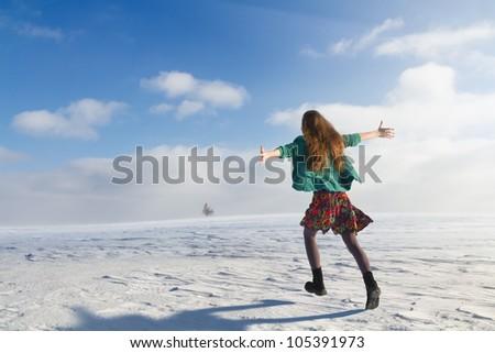 Girl jogging in snowy field - stock photo