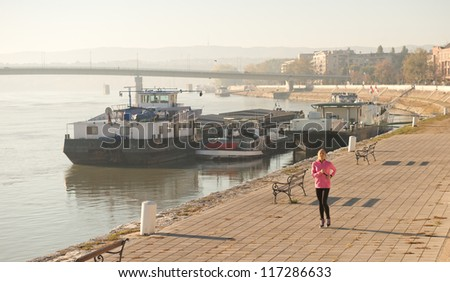 girl jogging on coasts river - stock photo