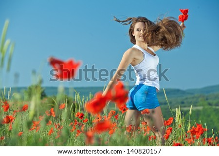 Girl jumping in poppy field over blue sky - stock photo