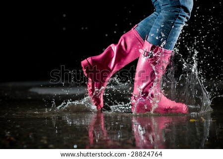 girl jumping in the puddle - stock photo