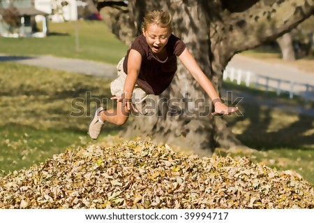 Girl Jumping into Autumn Leaves - stock photo