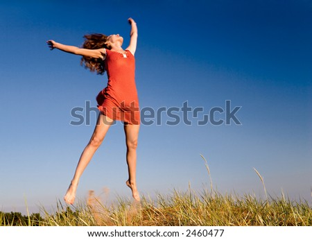 Girl jumping on a dune - stock photo