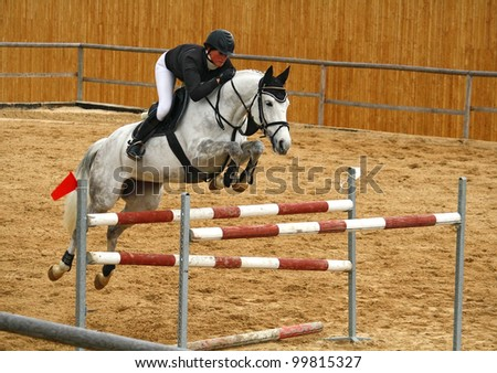 Girl jumping on a horse - stock photo