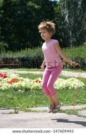 Girl jumping on a skipping rope in the park. - stock photo