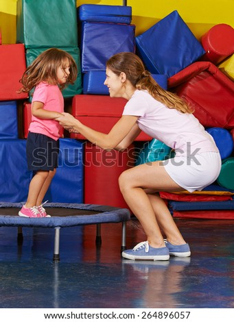 Girl jumping on trampoline with nursery teacher during children sports - stock photo