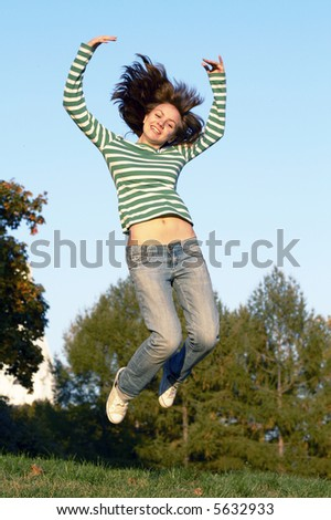 Girl jumping over a grass - stock photo