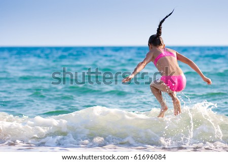 Girl jumping over sea wave. Summer, vacation - stock photo