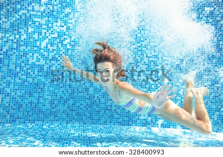 Girl jumps and swims in pool underwater, happy active child has fun in water, kid sport on family vacation  - stock photo